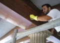 Cleaning the wood ceiling beams.